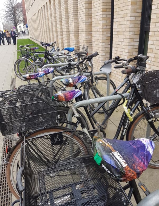 Portland Region-branded bicycle seat covers adorn every bike in a bike rack.
